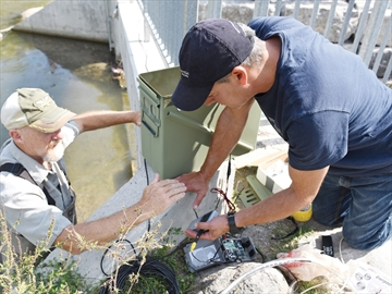Ryan Pfeiffer / Metroland BOWMANVILLE -- Dave Lawson, left, from the Bowmanville Conservation Group, helped Christopher Bunt, CEO of Biotactic Fish and Wildlife Research, test a camera system to record data for counting and identifying fish moving through the Bowmanville fish ladder. September 24, 2015.